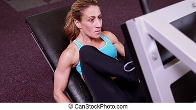 Super fit woman using the leg weights machine at the gym