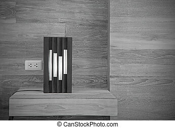 Black lamp on wooden shelf wall in black and white style