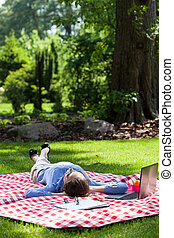 Woman lying on blanket and relaxing in garden - Working...
