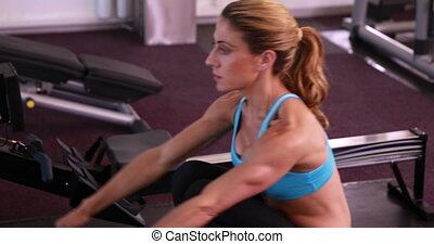 Fit woman using the rowing machine at the gym