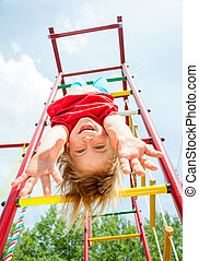 Happy child on a jungle gym - Little girl having fun playing...