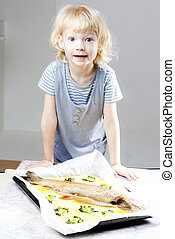 portrait of little girl with baked trout salmon