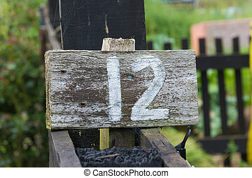 Wooden sign giving garden plot number
