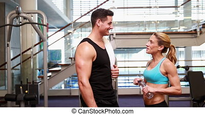 Super fit friends chatting together at the gym