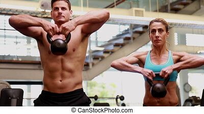 Two fit people lifting kettle bells together at the gym