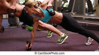 Two fit people lifting kettle bells together in plank...