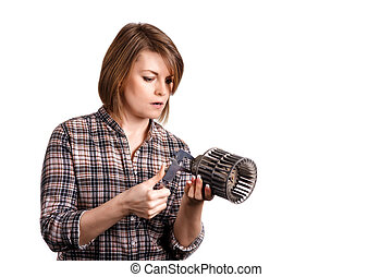 The girl mechanic with a caliper measures a car detail