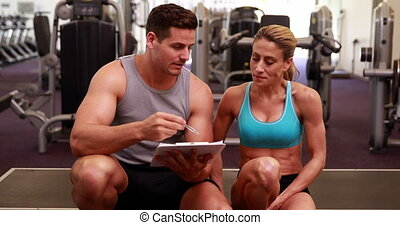 Fit woman and trainer talking about her progress at the gym