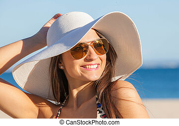 woman on vacation with  sun hat and glasses.