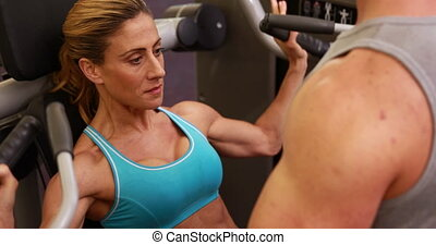 Fit woman using weight machine - Fit woman using weights...