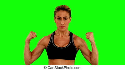 Super fit woman flexing her arms on green screen background