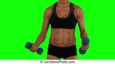 Super fit woman lifting dumbbells in black sports bra and...