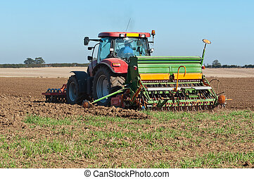 Seed Planting - Farmer in tractor with seed planter sowing a...