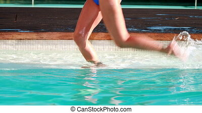 Woman splashing in the swimming pool on a sunny day