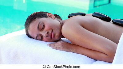 Peaceful brunette getting hot stone massage poolside on a...