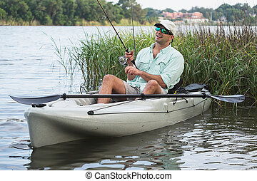 Man Fishing in Kayak - Man fishing from kayak on a beautiful...