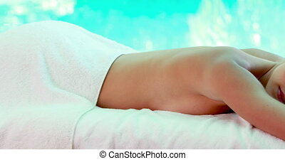 Peaceful blonde lying on massage table poolside on her...