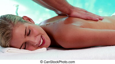 Peaceful blonde getting a massage poolside on her holidays