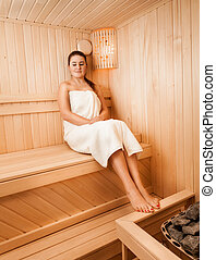 Woman in towel sitting on bench at sauna next to oven