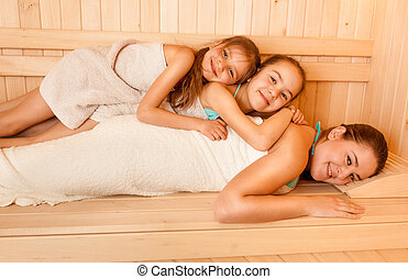 Little girls lying on mothers back at sauna - Portrait of...