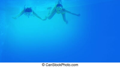 Happy friends in snorkels diving into swimming pool on their...