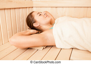 Portrait of brunette woman covered in towel lying at sauna -...