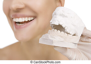 Woman holding a teeth sample - Woman holding denture model,...