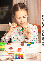 Photo of little diligent girl painting easter egg - Closeup...