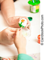 Women and child hands painting easter eggs - Closeup shot of...