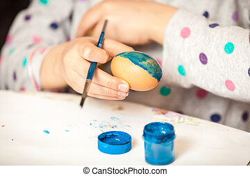 Shot of girl holding brush and painting ester egg - Closeup...
