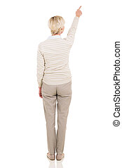 back view of senior woman pointing at empty copy space