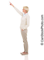 senior woman pointing up - side view of senior woman...