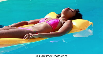 Gorgeous woman in swimming pool lying on lilo on her...
