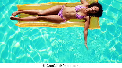 Gorgeous woman lying on lilo in swimming pool on her...