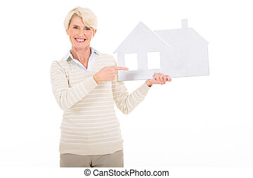 mature woman pointing white paper house - beautiful mature...