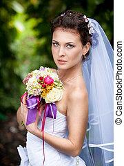 Portrait of cute bride with long veil holding bouquet