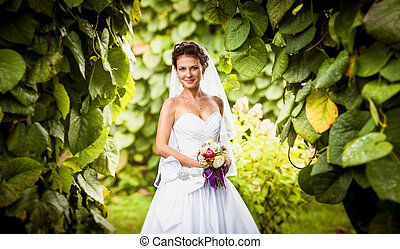 Portrait of smiling cute bride at park - Closeup portrait of...