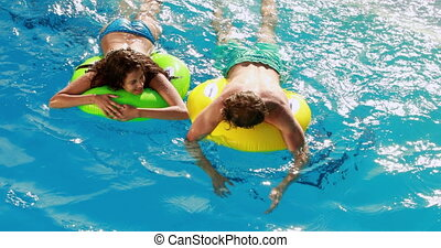 Couple swimming on inflatable rings in the pool on a sunny...