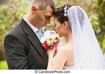 Portrait of sad bride and groom looking at bouquet
