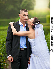 Portrait of bride kissing groom in cheek at park