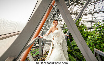 Bride standing under roof at greenhouse