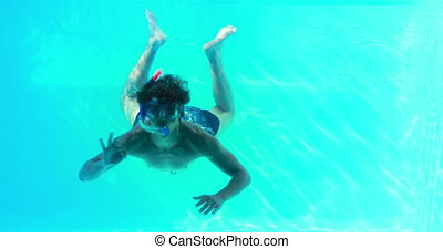 Man in snorkel jumping in swimming pool waving at camera on...