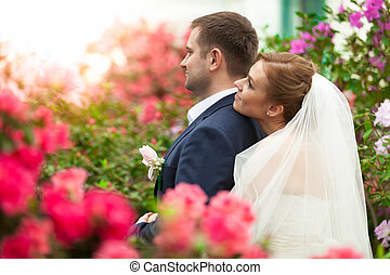 Bride holding groom from back among flower - Portrait of...