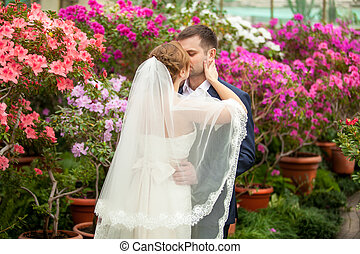 Newly married couple embracing among blooming trees -...