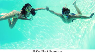 Happy couple jumping in swimming pool together wearing...