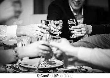 Hands clinking glasses at restaurant - Closeup black and...