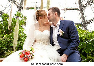 Just married couple kissing at orangery - Closeup portrait...