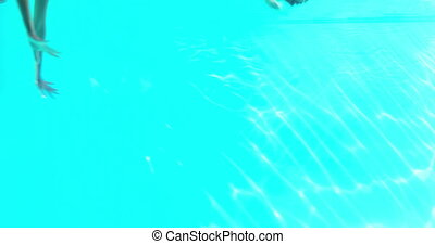 Happy couple jumping in swimming pool together on their...