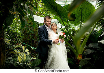 Groom holding bride under palms at jungle