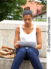 Young woman with tablet - Hispanic girl using tablet in the...
